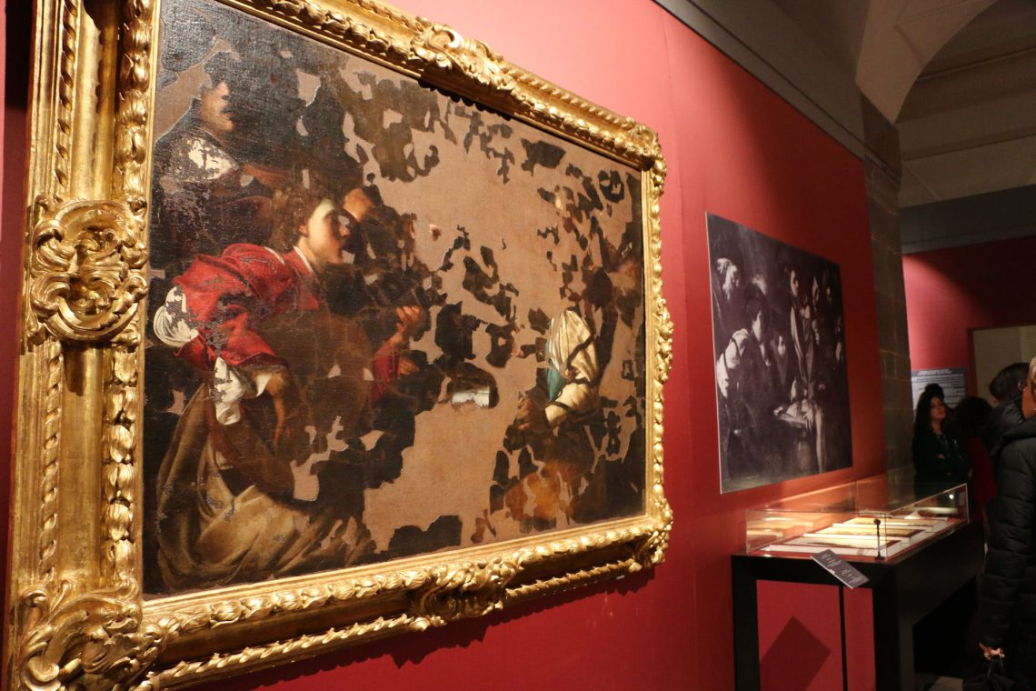 Two paintings, one heavily damaged and the other completely destroyed, on exhibit in the first section.